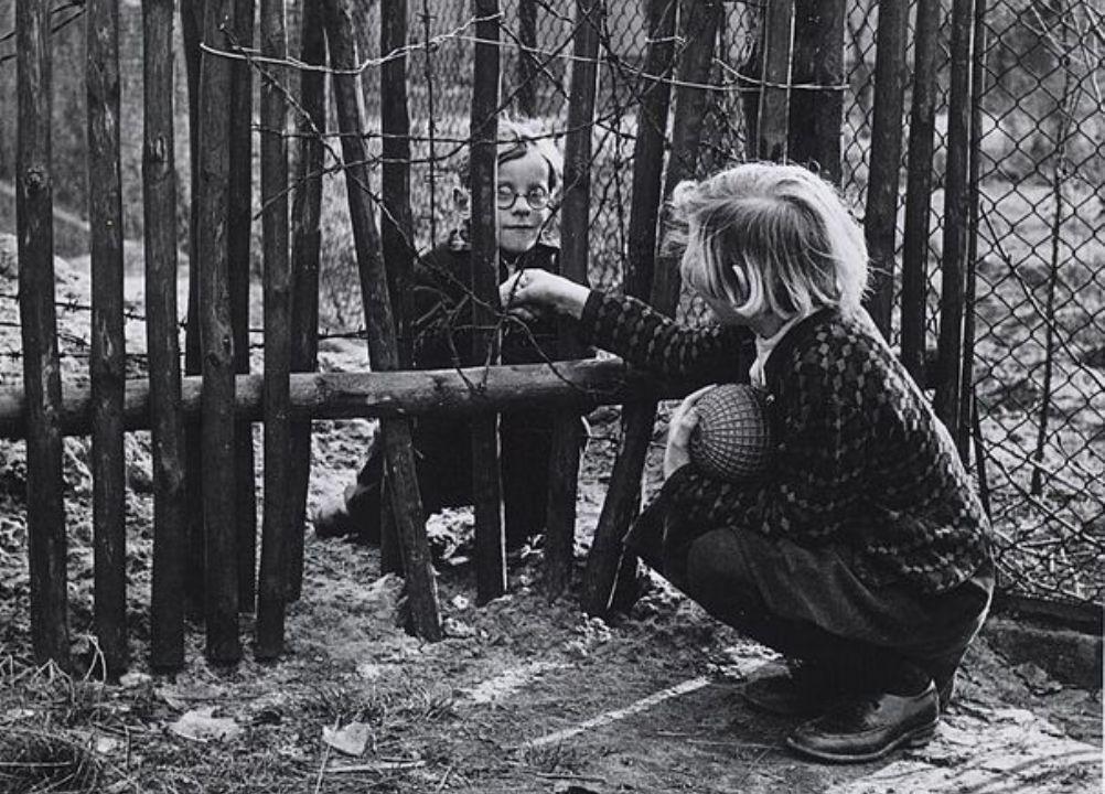 Een hekwerk scheidt deze kinderen uit Oost- en West Berlijn van elkaar in oktober 1961.