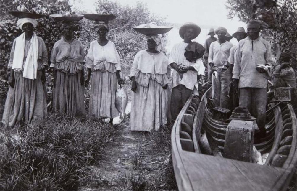 Een groep Creoolse visverkoopsters naast de vissers en hun boot in 1915. (foto: collectie Tropenmuseum)