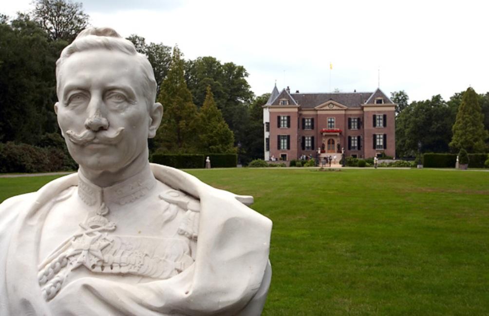 Een buste van de Duitse keizer Wilhelm II, met op de achtergrond Huis Doorn