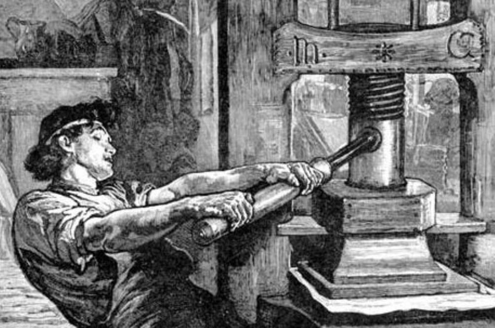 Een boekdrukker in de weer met een schroefdrukpers (foto: Wikimedia)