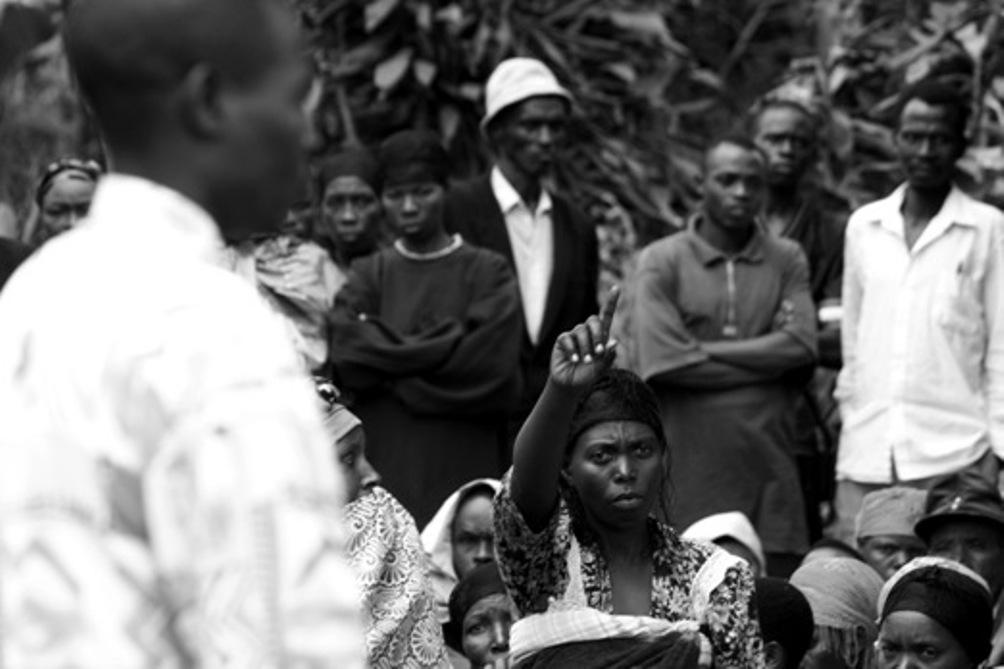 Een vrouw steekt haar vinger op om haar mening te delen tijdens een zitting van een volksrechtbank (gacaca) in 2006 in het Rwamagana district. (foto: Elisa Finocchiaro)