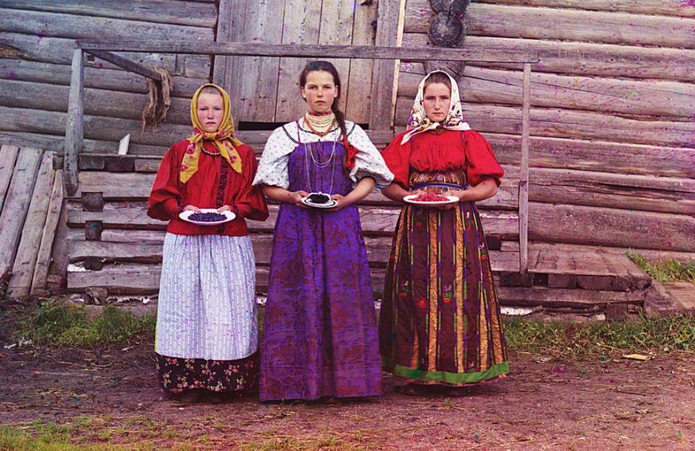 Drie jonge meisjes bieden de bezoekers van hun traditionele houten huis bessen aan, foto gemaakt in 1909 (foto: Library of Congress)