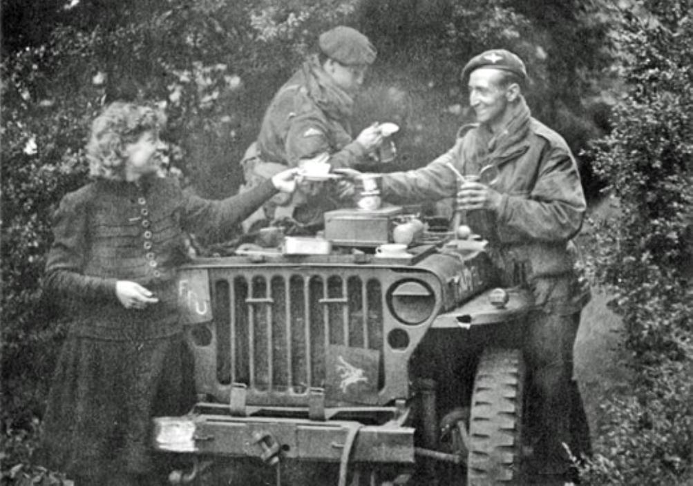 Een originele foto uit september 1944 waarop leden van de Army Film and Photographic Unit genieten van een kop thee aangeboden door mevrouw S.L. de Meulenaar. (foto: Imperial War Museum)