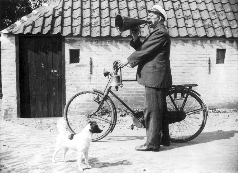 """Dorpsomroeper, West-Terschelling, 29 juli 1938. Op de foto maakt hij bekend dat het bergingsschip de """"Karimata"""" de eerste goudstaaf heeft gebaggerd van de vergane Lutine. (Spaarnestad Photo)"""