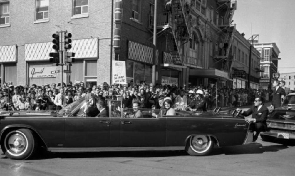 Foto van Secret Service-agent Clint Hill die achter op de bumper van de presidentiële limousine gehurkt zit tijdens de rit door Dallas (foto: Wikimedia)