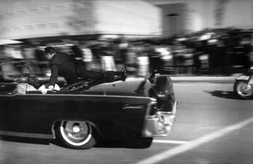 Secret Service-agent Clint Hill zit als een menselijk schild boven de dodelijk gewonde president en zijn vrouw, terwijl de presidentiële limousine op weg is naar het ziekenhuis (foto: Wikimedia).