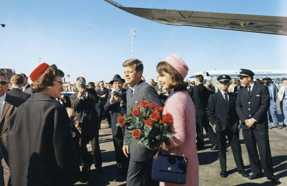 Kennedy en zijn vrouw Jaqueline komen aan op het vliegveld van Dallas, Texas. Daar staan de wagens voor de optocht klaar voor vertrek.