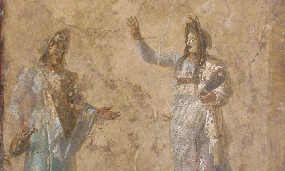 Acteurs dragen tragediemaskers met hoog opgestoken pruiken en een wanhopige oogopslag. (foto: Wikimedia)