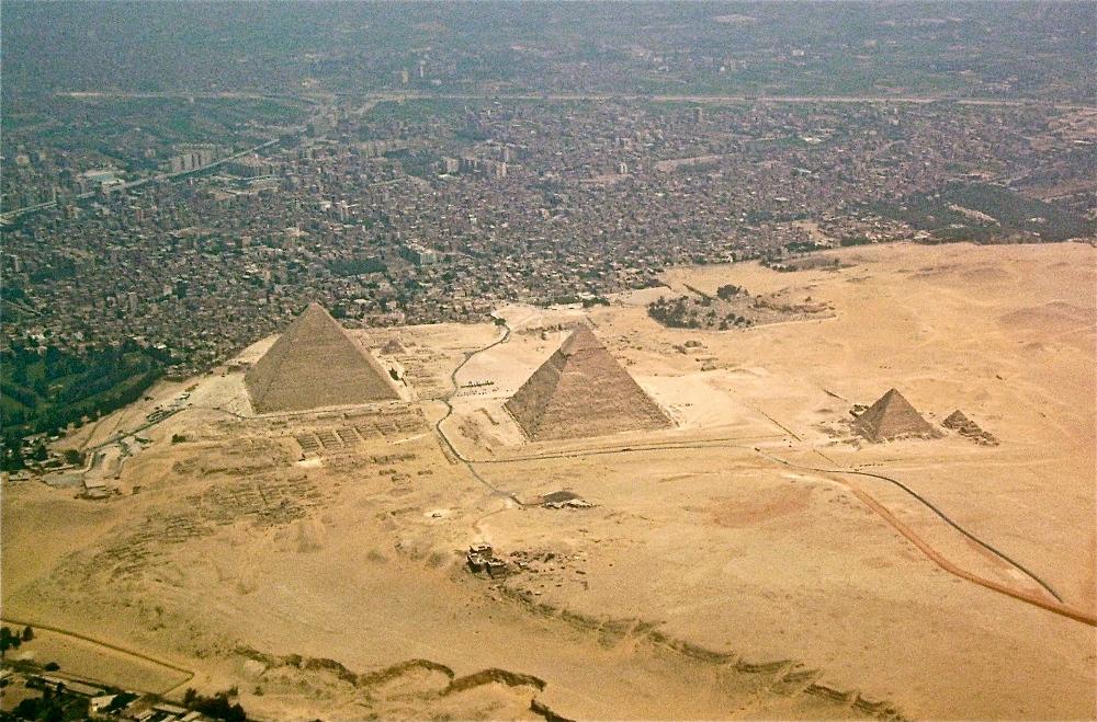 Op deze luchtfoto van het Gizeh plateau is duidelijk te zien hoe de grote stad de piramiden steeds verder opslokt.