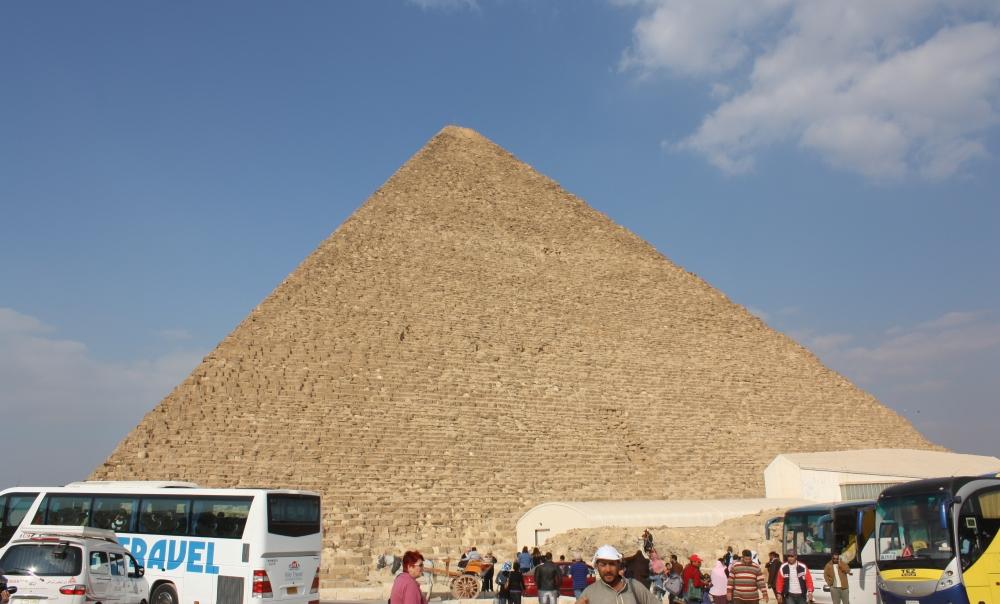 Bussen, toeristen, verkopers en kamelen: een realistisch beeld van de piramide van Cheops.