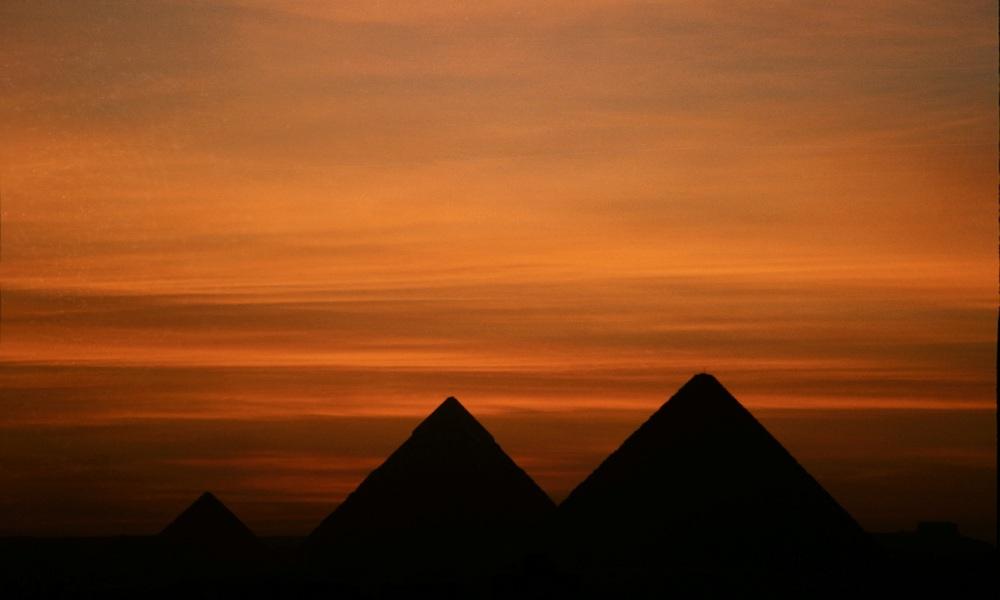 Silhouet van de piramiden in Gizeh bij zonsondergang. (foto: Wikimedia)