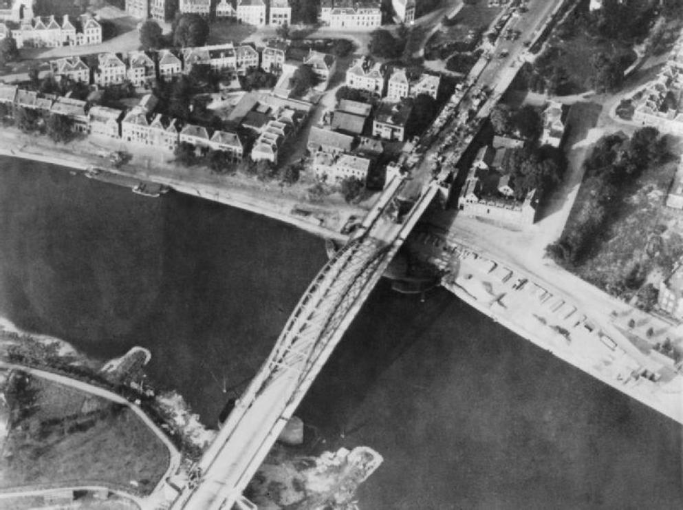 De brug bij Arnhem op 18 september 1944. Aan de bovenzijde van de brug zijn de wrakken van Duitse voertuigen te zien. (foto: Wikimedia)