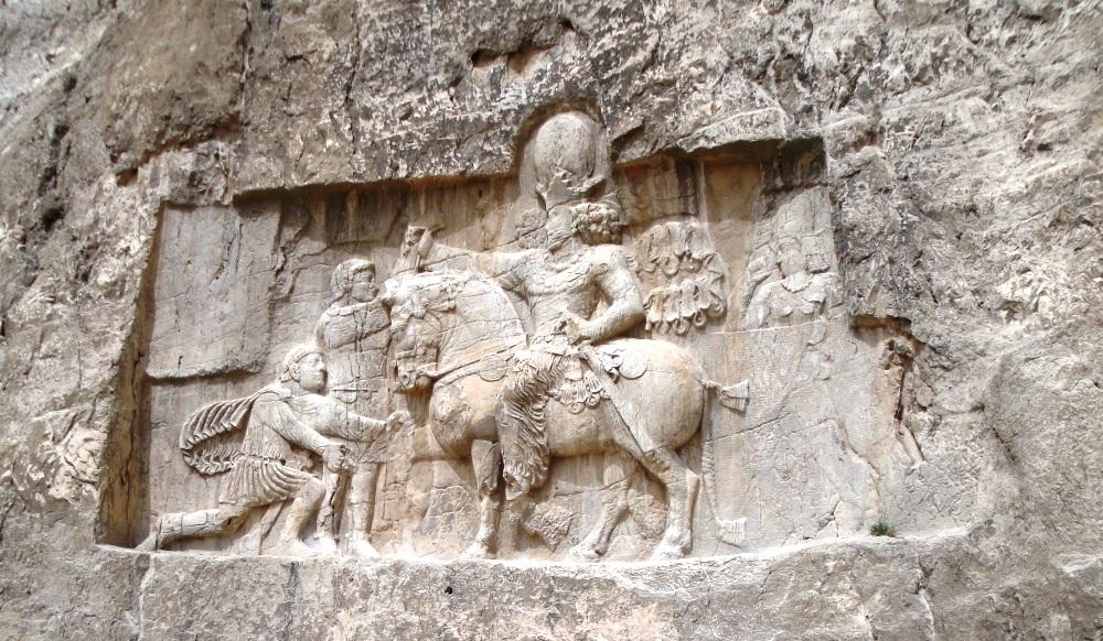 Bas-reliëf uit Naqš-i Rustam, het huidige Iran. Keizer Valerianus I (staand links) onderwerpt zich aan Shapur I die te paard zijn macht toont. (foto: Wikimedia)