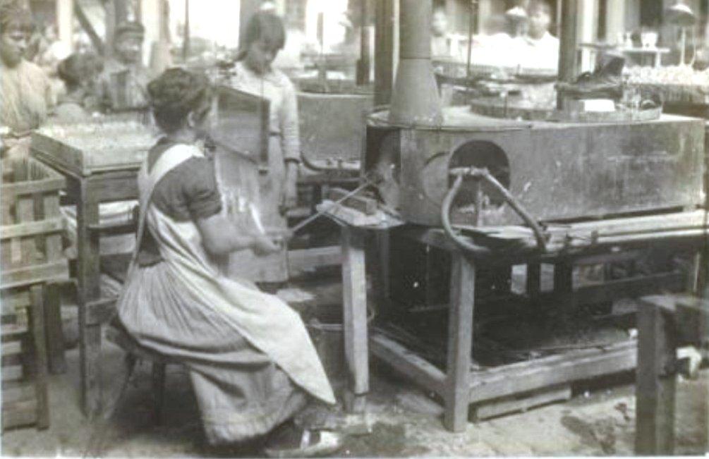 Het handmatig rondbranden van het glaswerk in de kristalfabriek van Sphinx. De 'plaat' voor de ogen van de arbeidster is de voorloper van de hedendaagse laskap (foto: Nationaal Archief)