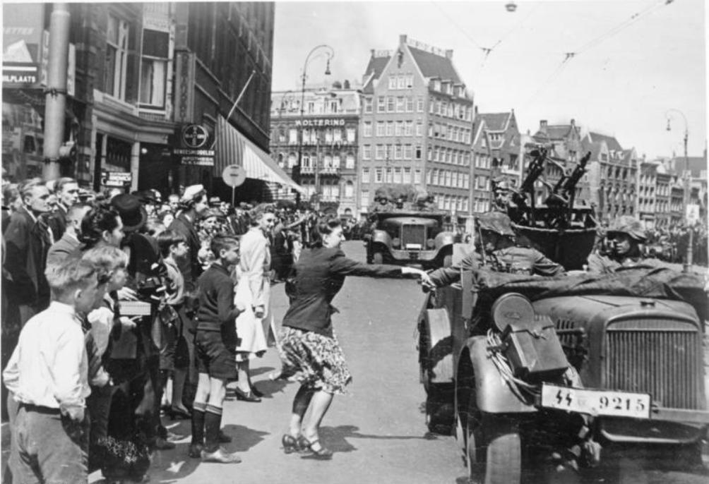 Een vrouw reikt een SS soldaat de hand, Amsterdam 1940. (foto: Bunderarchiv)